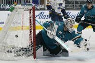 CORRECTS TO BRAYDEN SCHENN SCORED NOT PERRON - The puck crosses the net behind San Jose Sharks goaltender Devan Dubnyk on a goal scored by St. Louis Blues' Brayden Schenn (not shown) during the second period of an NHL hockey game in San Jose, Calif., Monday, March 8, 2021.(AP Photo/Jeff Chiu)
