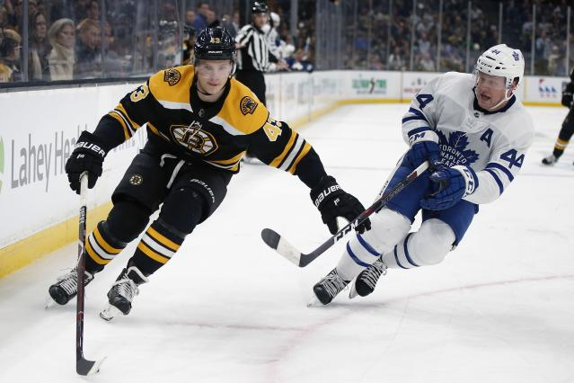 Toronto Maple Leafs' Morgan Rielly (44) defends against Boston Bruins' Danton Heinen (43) during the second period of an NHL hockey game in Boston, Saturday, Dec. 8, 2018. (AP Photo/Michael Dwyer)