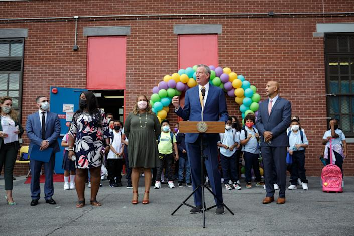 Mayor Bill de Blasio speaks on the first day of class at a school in the Bronx on Sept. 13, 2021 as his schools chancellor, Meisha Porter, looks on at his right. (Anna Watts/The New York Times)