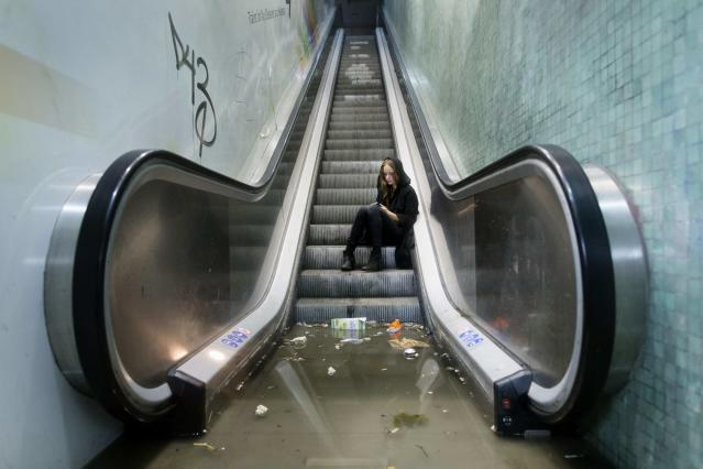 A woman calls for assistance after being trapped by water at a flooded Ryparken S-train station during a heavy rainstorm in Copenhagen August 31, 2014. REUTERS/Jens Astrup/Scanpix Denmark (DENMARK - Tags: TPX IMAGES OF THE DAY TRANSPORT ENVIRONMENT) DENMARK OUT. NO COMMERCIAL OR EDITORIAL SALES IN DENMARK. THIS IMAGE HAS BEEN SUPPLIED BY A THIRD PARTY. IT IS DISTRIBUTED, EXACTLY AS RECEIVED BY REUTERS, AS A SERVICE TO CLIENTS. NO COMMERCIAL SALES