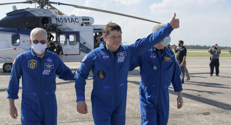 NASA astronaut Robert Behnken gives a thumbs up to onlookers as he boards a plane at Naval Air Station Pensacola to return him and NASA astronaut Douglas Hurley home to Houston a few hours after the duo landed in their SpaceX Crew Dragon Endeavour spacecraft off the coast of Pensacola, Fla., Sunday, Aug. 2, 2020. The Demo-2 test flight for NASA's Commercial Crew Program was the first to deliver astronauts to the International Space Station and return them safely to Earth onboard a commercially built and operated spacecraft. Behnken and Hurley returned after spending 64 days in space. (Bill Ingalls/NASA via AP)
