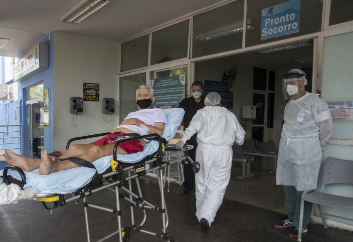 Health workers pull a COVID-19 patient from an ambulance into Santa Casa Hospital in Jau, Brazil, Thursday, Jan. 28, 2021. The Santa Casa hospital is operating at full capacity and patients take turns receiving oxygen. (AP Photo/Andre Penner)