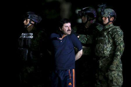 """Joaquin """"El Chapo"""" Guzman is escorted by soldiers during a presentation at the hangar belonging to the office of the Attorney General in Mexico City, Mexico January 8, 2016. REUTERS/Edgard Garrido"""