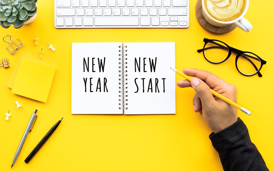 New year new start text with youngman writing on notepad on color desk table.Business goal-plan-action and resolution concepts ideas