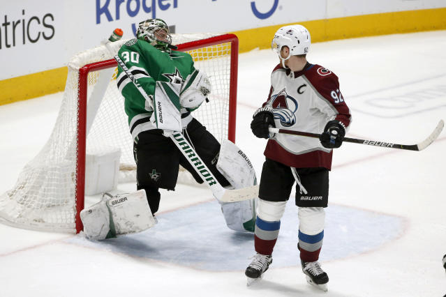 Dallas Stars goaltender Ben Bishop (30) makes a save off his head as Colorado Avalanche left wing Gabriel Landeskog (92) watches during the second period of an NHL hockey game in Dallas, Saturday, Dec. 28, 2019. (AP Photo/Michael Ainsworth)