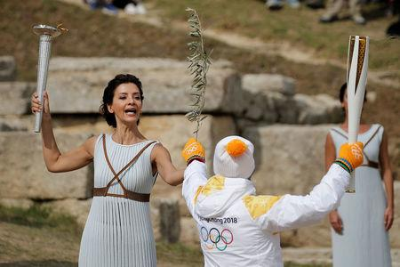 Olympics - Dress Rehearsal - Lighting Ceremony of the Olympic Flame Pyeongchang 2018 - Ancient Olympia, Olympia, Greece - October 23, 2017 Greek actress Katerina Lehou, playing the role of High Priestess, passes an olive branch to the first torchbearer, Greek cross country skiing athlete Apostolos Aggelis, during the dress rehearsal for the Olympic flame lighting ceremony for the Pyeongchang 2018 Winter Olympic Games at the site of ancient Olympia in Greece REUTERS/Alkis Konstantinidis
