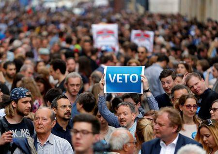 """A demonstrator holds up a banner saying """"Veto"""" during a rally against a new law passed by Hungarian parliament which could force the Soros-founded Central European University out of Hungary"""