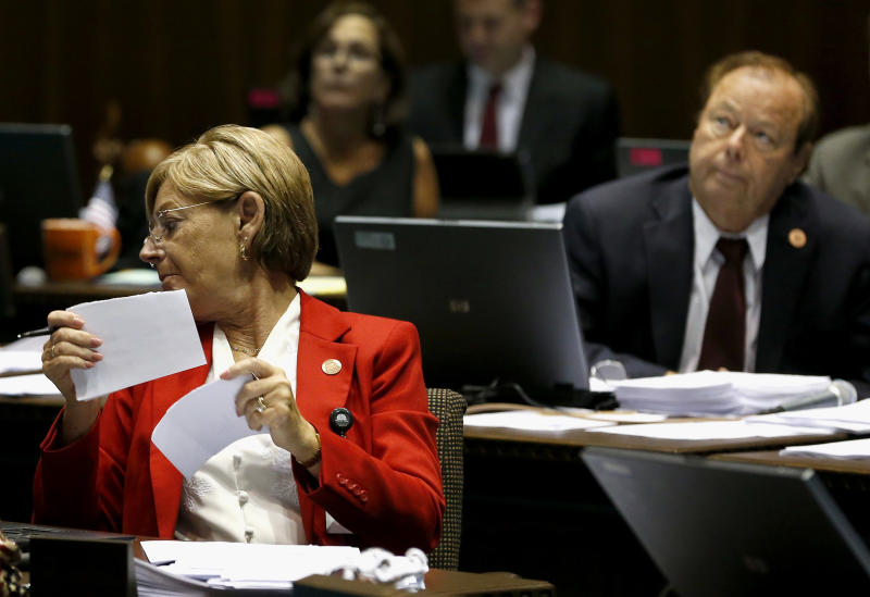 Rep. Karen Fann, R-Prescott, left, rips up an amendment to a bill that is pulled prior to vote, as Rep. Frank Pratt, R-Casa Grande, looks up in a special session budget battle for Medicaid funding on Wednesday, June 12, 2013, in Phoenix. The Arizona Legislature is on track to pull an all-nighter and work into Thursday to finish a state budget and approve Medicaid expansion. (AP Photo/Ross D. Franklin)