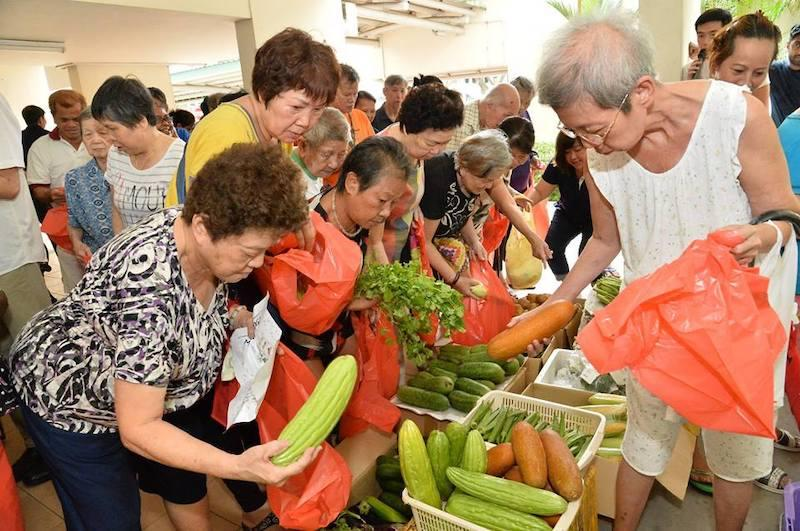 Residents of Dorset Road are busy snapping up the 300kg of fresh fruits and vegetables that were given out to needy residents (Photo: Melvin Yong / Facebook)
