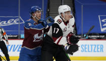 Arizona Coyotes center Tyler Pitlick, right, reacts as Colorado Avalanche defenseman Dan Renouf tries to clear him from in front of the net in the second period of an NHL hockey game Monday, March 8, 2021, in downtown Denver. (AP Photo/David Zalubowski)