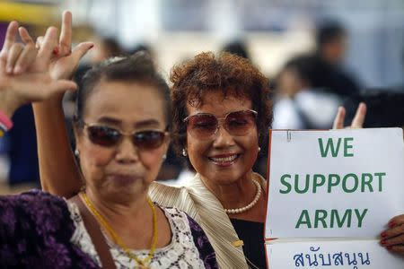 Supporters of the military gesture as they hold up a sign during a reconciliation event organized by the military at a shopping mall in Bangkok