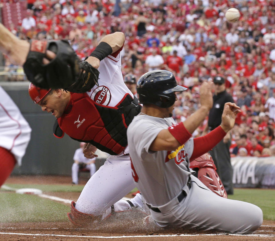 St. Louis Cardinals' Jon Jay, right, is safe at home as the ball gets away from Cincinnati Reds catcher Devin Mesoraco in the first inning of a baseball game, Saturday, Aug. 3, 2013, in Cincinnati. Jay scored on a double by Carlos Beltran. (AP Photo/Al Behrman)