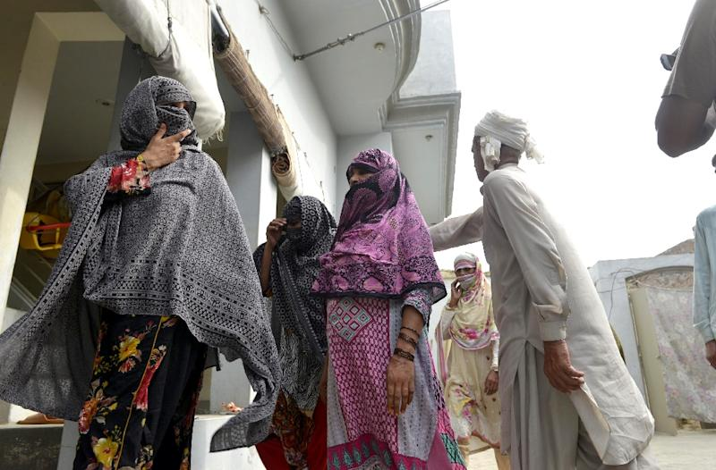 Villagers gather at a house after the authorities announced a judicial inquiry into a massive child abuse scandal in Hussain Khanwala village, some 55 kms southwest of Lahore on August 9, 2015 (AFP Photo/Arif Ali)