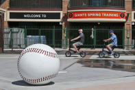 FILE - Matt Kirmer, left, and Joe Lieser, right, both of Torrance, California, ride scooters past Scottsdale Stadium, the spring training home of the San Francisco Giants, in Scottsdale, Ariz., in this Saturday, March 14, 2020, file photo. Big league managers say that Major League Baseball has instructed them to prepare for spring training to start on time in mid-February despite uncertainty around the coronavirus. Tampa Bay Rays manager Kevin Cash said Wednesday, Dec. 16, 2020, that officials from the commissioner's office had a meeting with managers Tuesday an expressed optimism about opening spring camps as scheduled. (AP Photo/Sue Ogrocki, File)