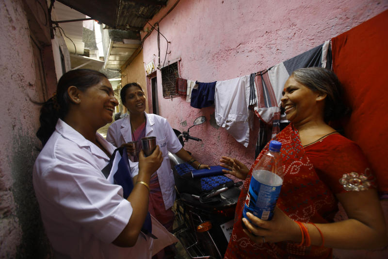 "In this Tuesday, May 21, 2013 photo, Usha Devi, right, who was suffering from cervical cancer, talks with health workers from Tata Memorial Hospital in a slum in Mumbai, India. A simple vinegar test slashed cervical cancer death rates by one-third in a remarkable study of 150,000 women in the slums of India, where the disease is the top cancer killer of women. Experts called the outcome ""amazing"" and said this quick, cheap test could save tens of thousands of lives each year in developing countries by spotting early signs of cancer, allowing treatment before it's too late. Devi, one of the women in the study, says it saved her life.  (AP Photo/Rafiq Maqbool)"