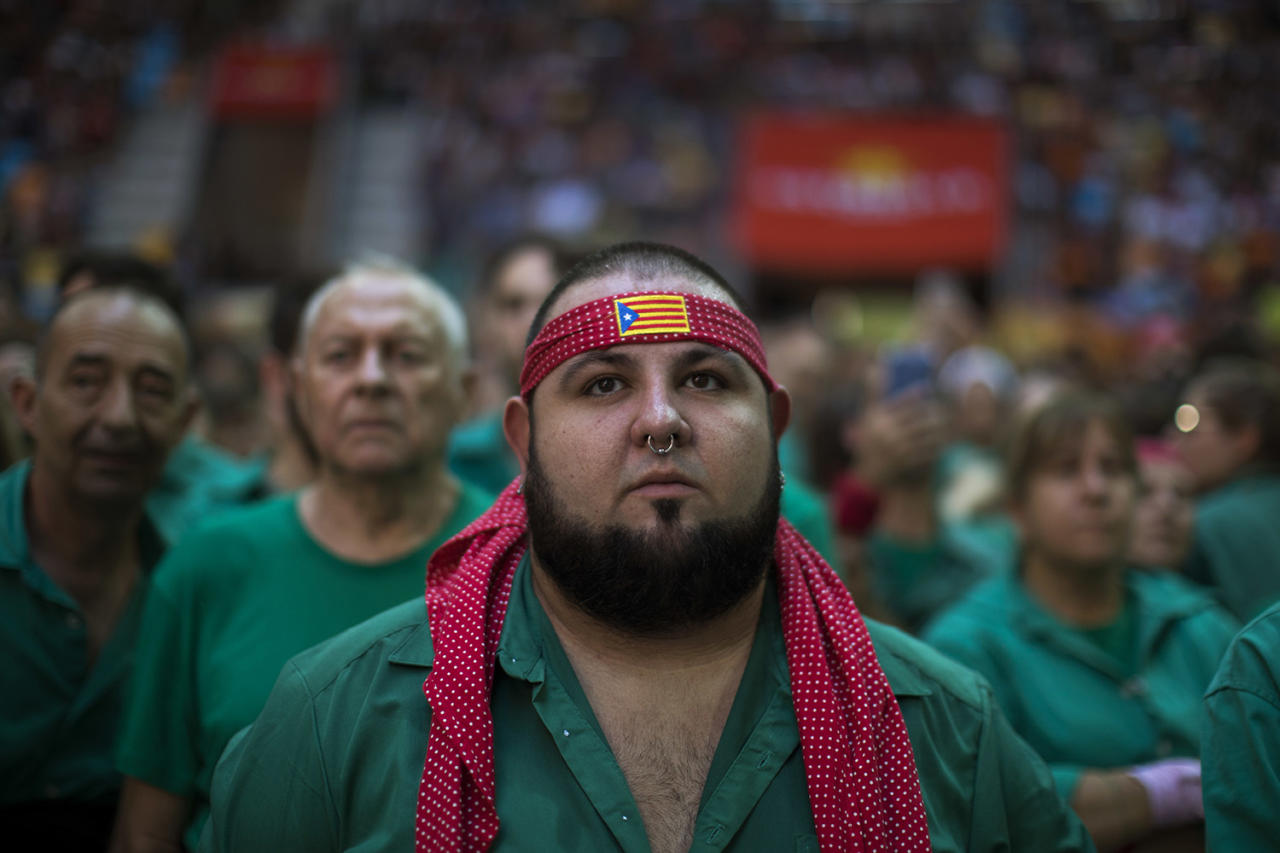 <p>Arnau Cornado, 24, looks as members of the Castellers de Terrassa try to complete their human tower, during the 27th Human Tower Competition in Tarragona, Spain on Oct. 6, 2018. (Photo: Emilio Morenatti/AP) </p>