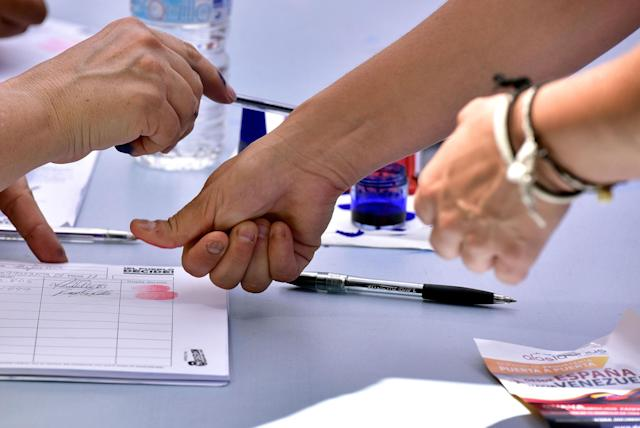 <p>A Venezuelan resident in Madrid stamps fingerprint at a polling station during a symbolic plebiscite on president Maduro's project of a future constituent assembly, called by the Venezuelan opposition and held at the Puerta del Sol in Madrid on July 16, 2017. (Gerard Julien/AFP/Getty Images) </p>