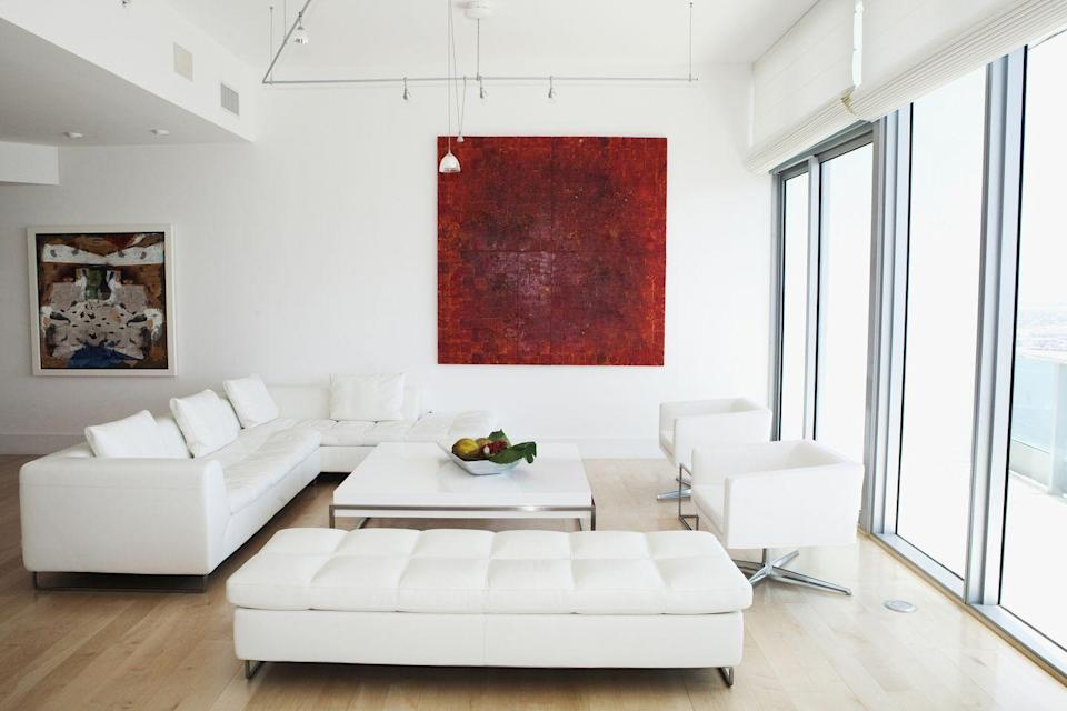 """<p>You love your art, but do you love it more than a healthy dose of vitamin D? Save your large, dark artworks for rooms that aren't short on light. If you cover a wall with paintings or posters, they <a href=""""http://www.nytimes.com/2012/01/05/garden/not-much-natural-light-tips-to-make-your-place-look-brighter.html"""" rel=""""nofollow noopener"""" target=""""_blank"""" data-ylk=""""slk:will absorb the little sunlight"""" class=""""link rapid-noclick-resp"""">will absorb the little sunlight</a> streaming into your space rather than reflect it. </p>"""