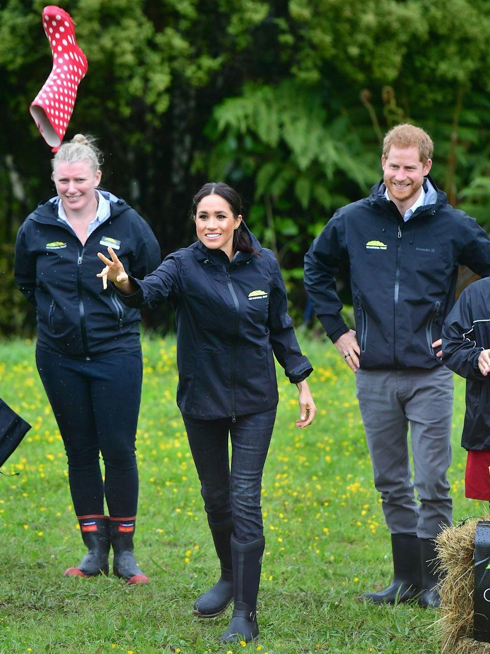 <p>Meghan throws the gumboot during the contest as Prince Harry looks on. </p>