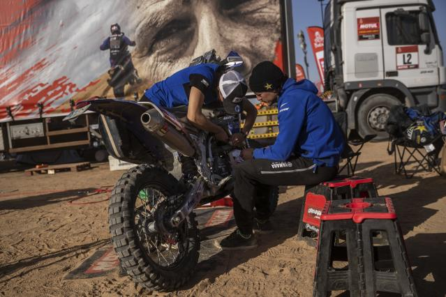 "In this Monday, Jan. 13, 2020 photo, Sara Garcia of Spain checks her Yamaha motorbike, next to his partner Javier Vega of Spain at the Dakar rally ""park ferme"" in Wadi Al Dawasir, Saudi Arabia. Formerly known as the Paris-Dakar Rally, the race was created by Thierry Sabine after he got lost in the Libyan desert in 1977. Until 2008, the rallies raced across Africa, but threats in Mauritania led organizers to cancel that year's event and move it to South America. It has now shifted to Saudi Arabia. The race started on Jan. 5 with 560 drivers and co-drivers, some on motorbikes, others in cars or in trucks. Only 41 are taking part in the Original category. (AP Photo/Bernat Armangue)"