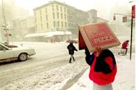 <p>Either a pizza delivery man or customer (either way this is epic) shields himself from an unexpected blizzard pounding with an empty pizza box. We're not sure if you can get any more New York than this. </p>