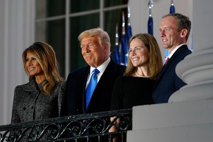 First lady Melania Trump, President Donald Trump, Amy Coney Barrett and Jesse Barrett stand on the Blue Room Balcony after Supreme Court Justice Clarence Thomas administered the constitutional oath on the South Lawn of the White House in Washington.