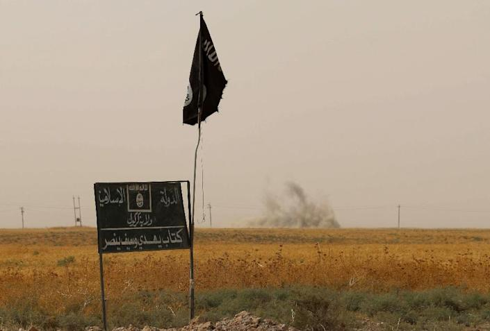 Smoke rises in the distance behind an Islamic State (IS) group flag in the district of Daquq, south of the northern Iraqi multi-ethnic city of Kirkuk on September 11, 2015 (AFP Photo/Marwan Ibrahim)