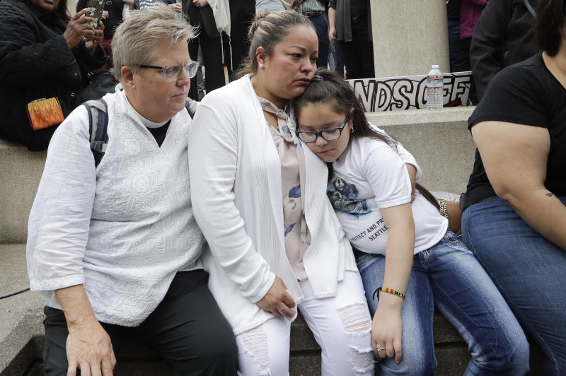 In this photo taken Wednesday, July 17, 2019, Gethsemane Lutheran Church Pastor Joanne Engquist, left, sits with Susana Robles and her daughter Natalie Robles, after their husband and father, Jose Robles, turned himself in to immigration authorities in Tukwila, Wash. The prospect of nationwide immigration raids has provided evidence that legions of pastors, rabbis and their congregations stand ready to help vulnerable immigrants with offers of sanctuary and other services. (AP Photo/Elaine Thompson)
