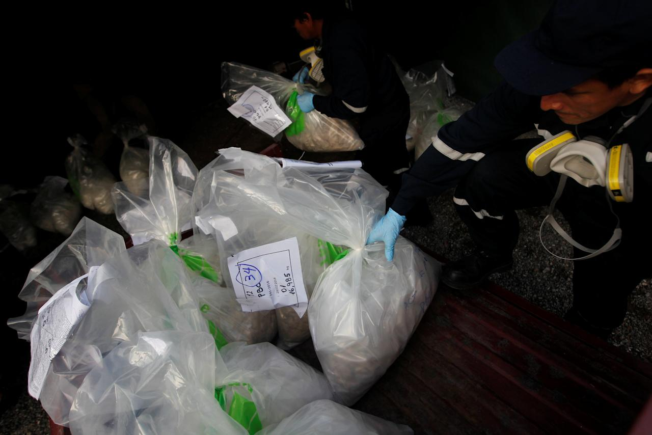 Anti-narcotics workers carry bags containing cocaine and other drugs during an incineration of about 7.9 tons, seized during police operations, according to the Interior Ministry, in Lima, Peru February 2, 2017. REUTERS/Guadalupe Pardo