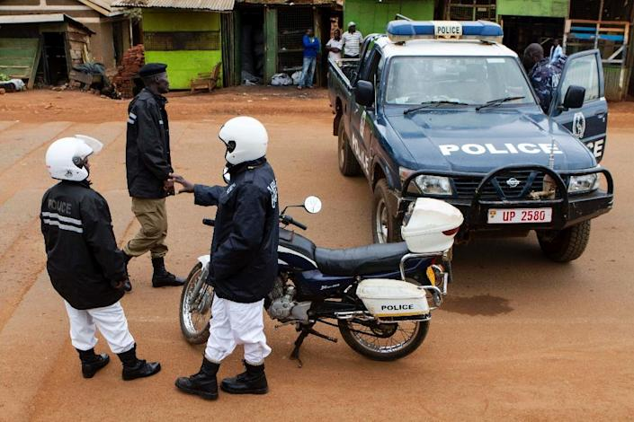 Police stand guard at the scene where acting assistant director of public prosecution Joan Kagezi was shot dead in a suburb in Kampala, on March 31, 2015 (AFP Photo/Isaac Kasamani)