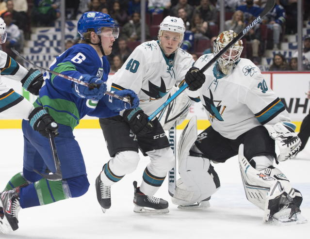 San Jose Sharks center Antti Suomela (40) tries to clear Vancouver Canucks right wing Brock Boeser (6) from in front of Sharks goaltender Aaron Dell (30) during the second period of an NHL hockey game Saturday, Jan. 18, 2020, in Vancouver, British Columbia. (Jonathan Hayward/The Canadian Press via AP)