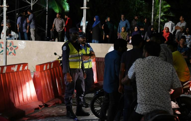 Security forces stand outside the office of the Maldivian Democratic Party, the island nation's beleaguered opposition