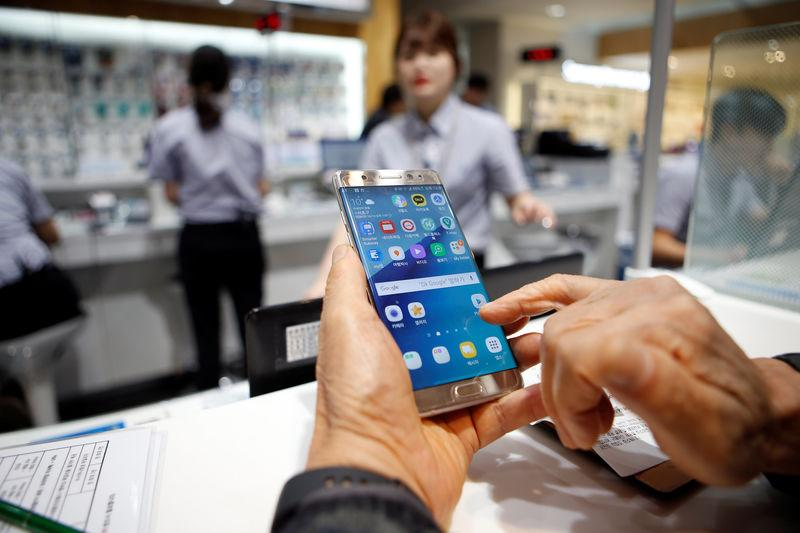 A customer uses his Samsung Electronics' Galaxy Note 7 as he waits for exchange at company's headquarters in Seoul