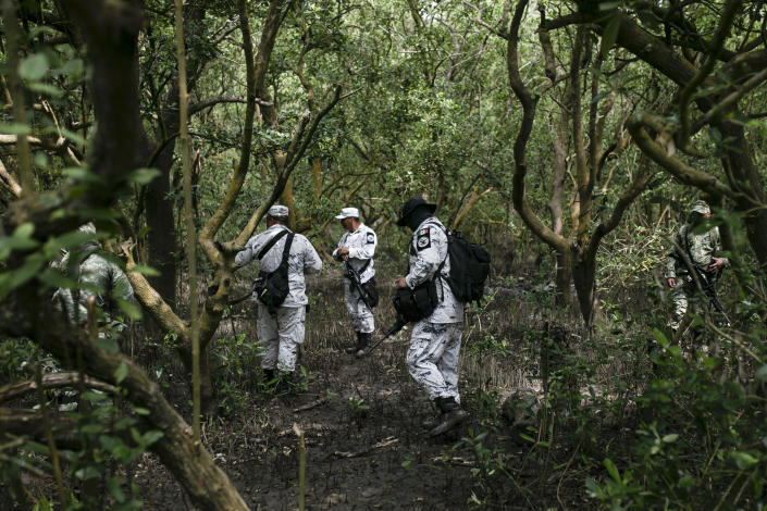Soldiers of the Mexican Army and members of the National Guard search for possible clandestine gravesites in Puquita a tropical mangrove island, near Alvarado in the Gulf coast state of Veracruz, Mexico, Thursday, Feb. 18, 2021. Investigators from the National Search Commission found three pits with human remains and plastic bags inside. The number of bodies there has not yet been determined. (AP Photo/Felix Marquez)