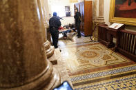 FILE - In this Jan. 6, 2021, file photo U.S. Capitol Police hold insurrectionists loyal to President Donald Trump at gun-point near the House Chamber inside the U.S. Capitol in Washington. A month ago, the U.S. Capitol was besieged by Trump supporters angry about the former president's loss. While lawmakers inside voted to affirm President Joe Biden's win, they marched to the building and broke inside. (AP Photo/Andrew Harnik, File)