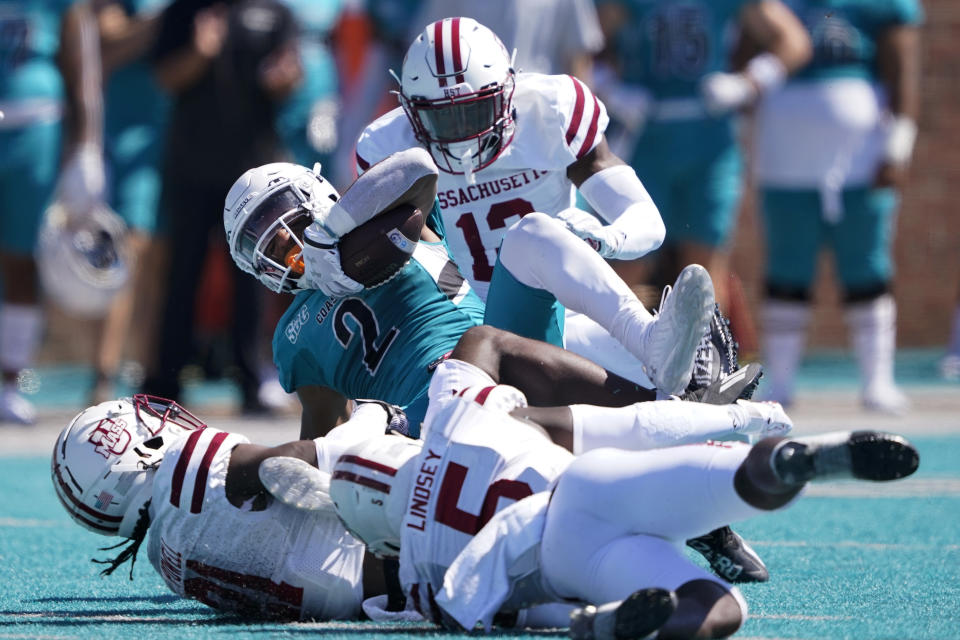 Coastal Carolina running back Reese White is tackled by Massachusetts during the first half of an NCAA college football game on Saturday, Sept. 25, 2021, in Conway, S.C. (AP Photo/Chris Carlson)