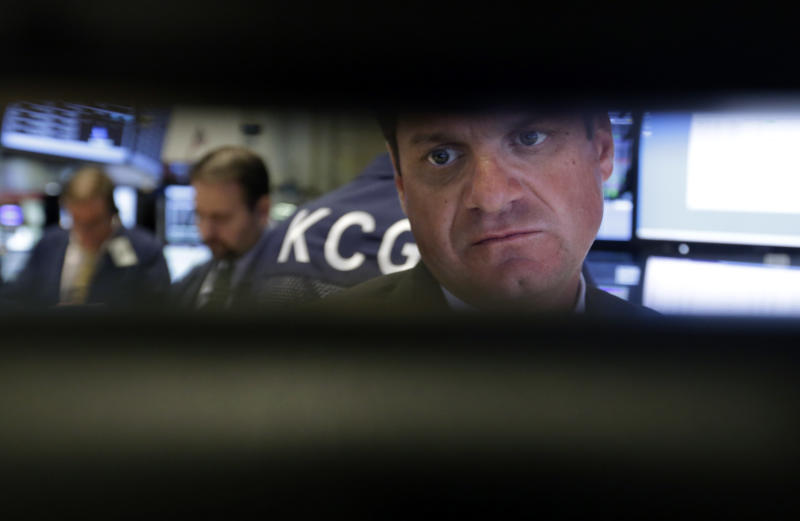 FILE - In this Wednesday, Sept. 18, 2013, file photo, specialist Michael Guli, right, is framed by his monitors as he works at his post on the floor of the New York Stock Exchange. Global stock markets fell Wednesday, Sept. 25, 2013 dragged down by fears that political gridlock in Washington over the federal budget might shut down the U.S. government. (AP Photo/Richard Drew)