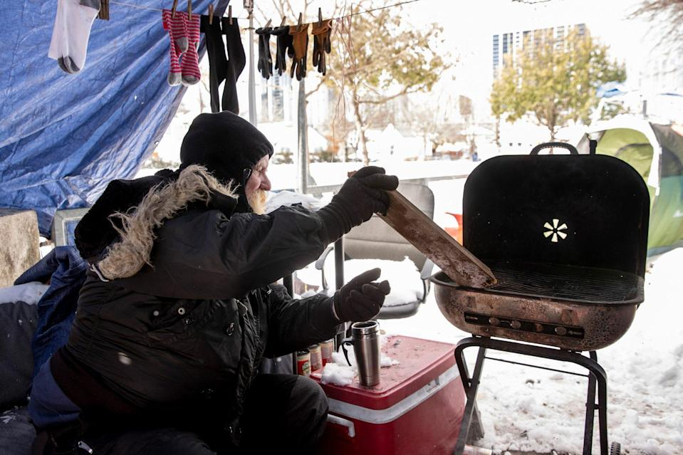 <p>A man tends a fire he used for heat and cooking at a homeless camp in Austin, Texas, after the extreme cold snap. </p>