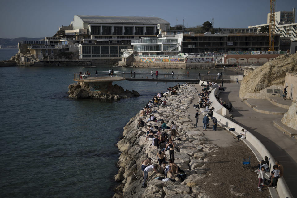 """Sunbathers sit by the Plage des Catalans in Marseille, southern France, Friday, April 2, 2021. With France now Europe's latest virus danger zone, Macron on Wednesday ordered temporary school closures nationwide and new travel restrictions. But he resisted calls for a strict lockdown, instead sticking to his """"third way"""" strategy that seeks a route between freedom and confinement to keep both infections and a restless populace under control until mass vaccinations take over. (AP Photo/Daniel Cole)"""