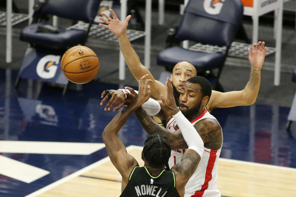 Houston Rockets guard John Wall (1) passes out of pressure from Minnesota Timberwolves guards Jaylen Nowell (4) and Jordan McLaughlin (6) in the first quarter during an NBA basketball game, Friday, March 26, 2021, in Minneapolis. (AP Photo/Andy Clayton-King)