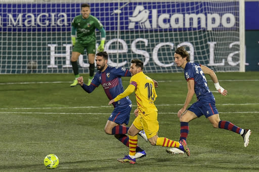 Barcelona's Lionel Messi, center, in action during the Spanish La Liga soccer match between Huesca and FC Barcelona at El Alcoraz stadium in Huesca, Spain, Sunday, Jan. 3, 2021. (AP Photo/Alvaro Barrientos)