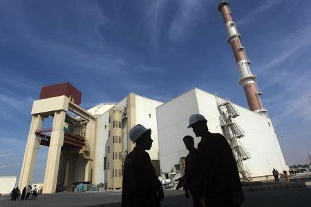 Iranian workers stand in front of Bushehr nuclear power plant, 1,200 km south of Tehran