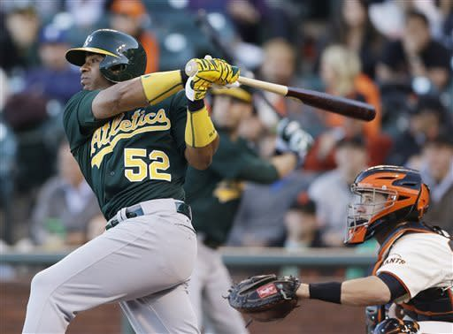 Oakland Athletics' Yoenis Cespedes watches his RBI triple in front of San Francisco Giants catcher Buster Posey during the first inning of a baseball game Wednesday, May 29, 2013, in San Francisco. (AP Photo/Eric Risberg)