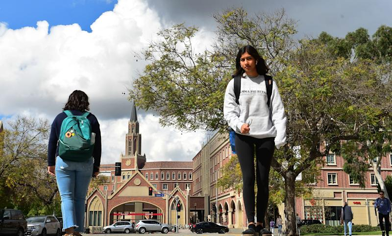 Students walk on the campus at the University of Southern California (USC) in Los Angeles, California on March 11, 2020, where a number of southern California universities, including USC, have suspended in-person classes due to coronavirus concerns. (Frederic J. Brown/AFP via Getty Images)