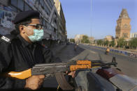 A police officer stands guard in a business district to ensure a lockdown to help control the spread of the coronavirus, in Karachi, Pakistan, Sunday, May 9, 2021. (AP Photo/Fareed Khan)