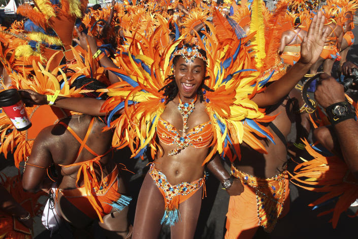PORT OF SPAIN, TRINIDAD - FEBRUARY 17:  Masqueraders from the band 'Ah Come Back Home' by Ronnie & Caro dance in the Queen's Park Savannah during the Parade of Bands as part of Trinidad and Tobago Carnival on February 17, 2015 in Port of Spain, Trinidad. (Photo by Sean Drakes/LatinContent via Getty Images)