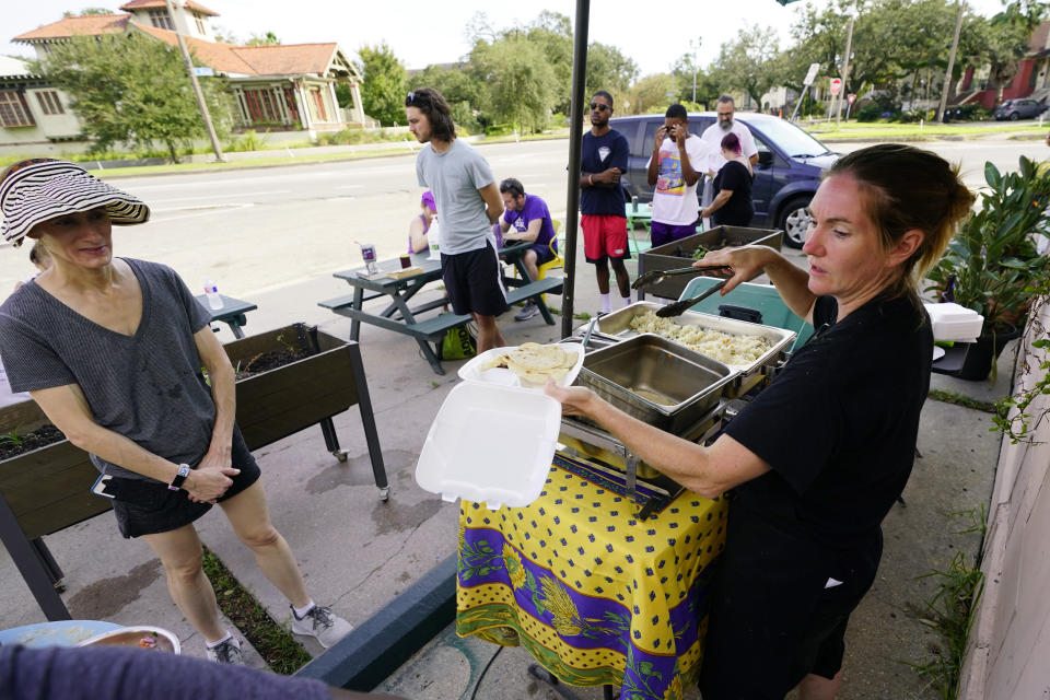 """In this Wednesday, Sept. 1, 2021, photo, El Pavo Real restaurant owner Lindsey McLellan, right, used food preserved """"with ice and prayer"""" to serve up a free steak taco meal, in New Orleans, La. In New Orleans, food is just one of the many ways that residents help each other during hard times. And it's been no different in the days after Hurricane Ida, which flooded or destroyed homes, tore up trees and knocked out the entire city's power grid.(AP Photo/Eric Gay)"""