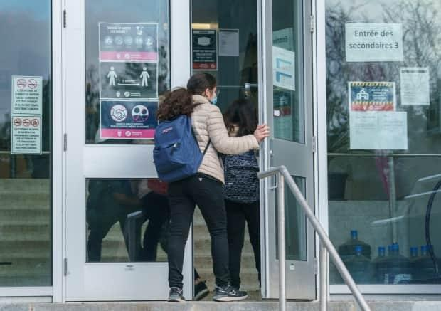 A student is seen entering Pierre Laporte Secondary School in Montreal last month.  Quebec is aiming to vaccinate teens as early as this summer. (Paul Chiasson/The Canadian Press - image credit)