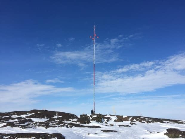A meteorological evaluation tower in Sanikiluaq. The wind monitoring tower was installed several years ago to determine whether the community was a good fit for wind turbines.  (Qikiqtaaluk Business Development Corp.  - image credit)