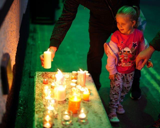 Members of the public light candles as they attend a vigil for the community in Plymouth, Devon (Ben Birchall/PA)